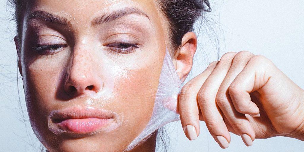Жена, която отлепва маска от лицето си